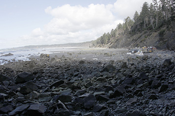 A landscape view of the rugged Washington coast, with cleanup workers dismantling the dock and removing plastic foam to the right.