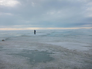 Man in the distance walking on sea ice.