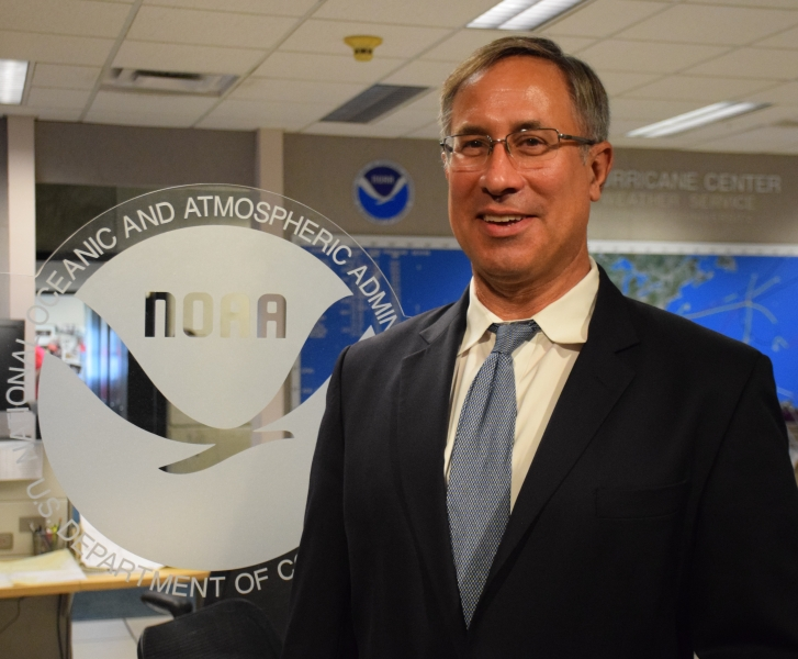 A man standing next to a NOAA logo.
