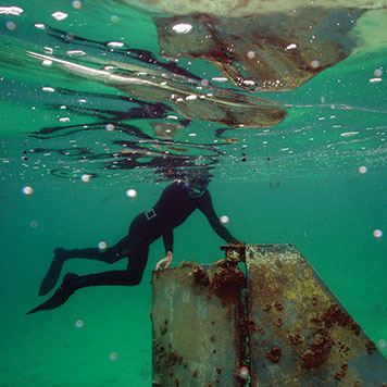 Diver exploring an abandoned vessel. (NOAA)