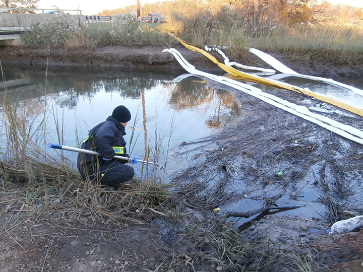 Man crouching and holding a scoop on a creek marsh shore with oil and boom in the water.