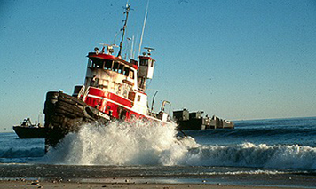 The tug Scandia aground on a beach in the pounding surf.