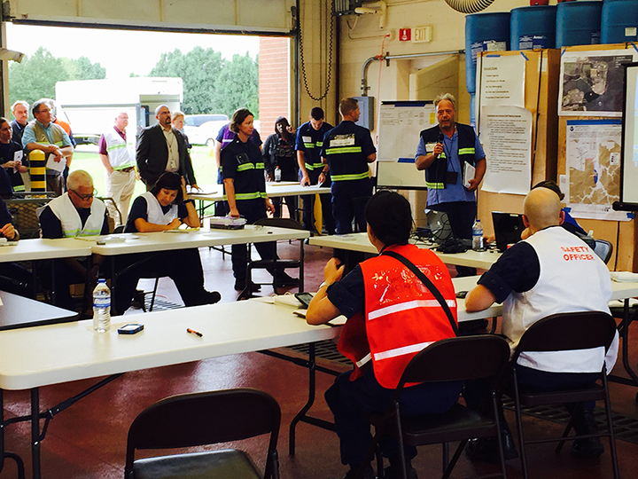 Group of responders in safety vests standing and sitting around tables.