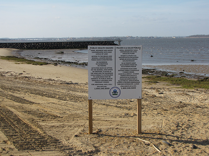 Public health hazard sign about lead contamination on a beach and jetty.