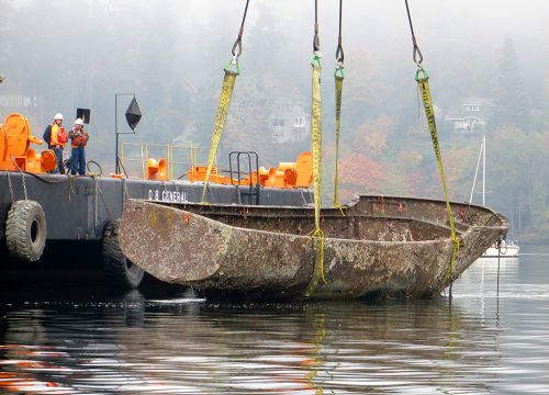A derelict vessel being pulled out of the water.