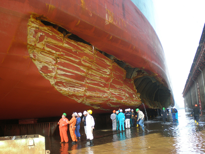 People observe a large tanker with a huge gash in its hull in dry dock.