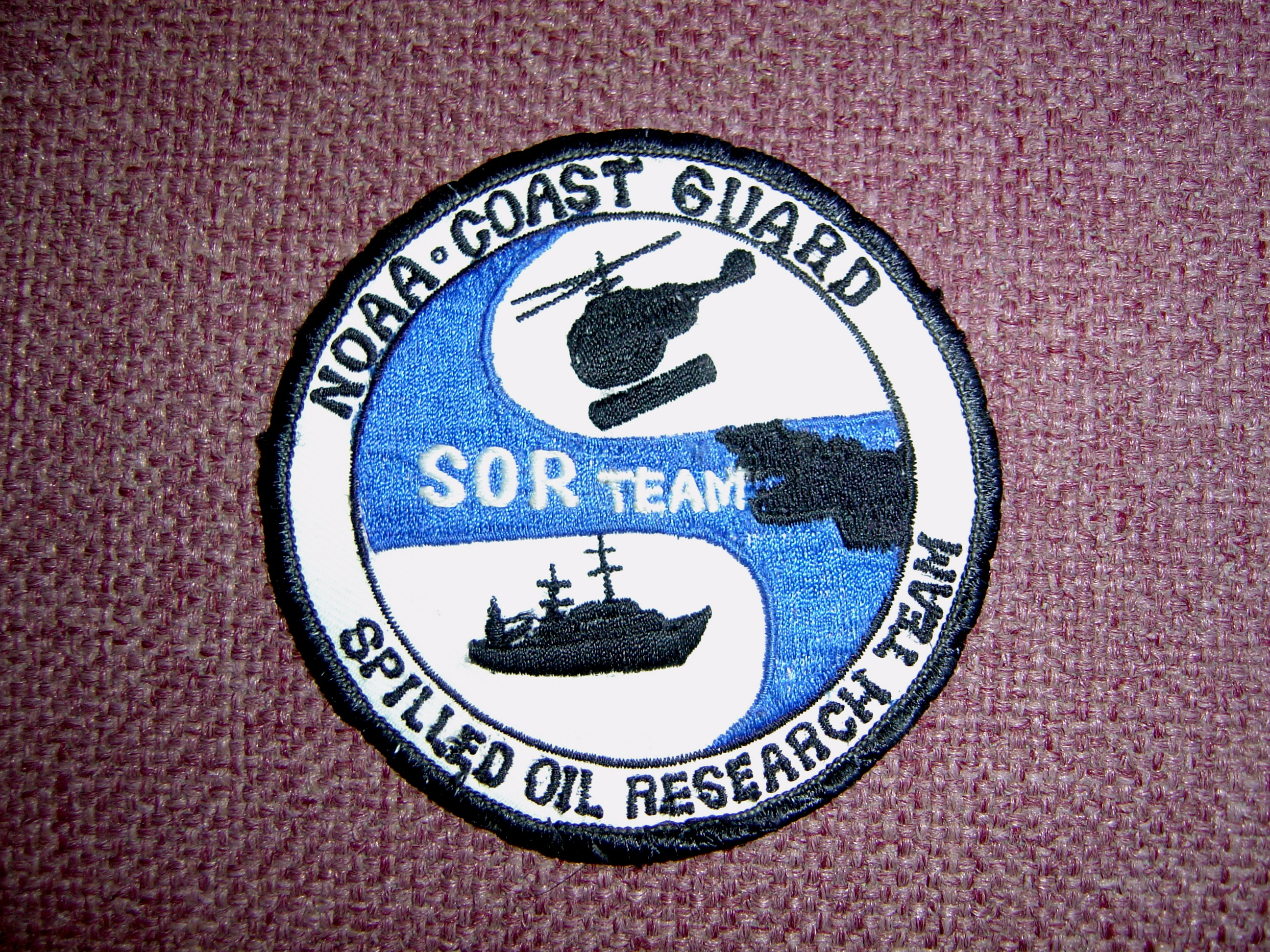 A cloth badge showing a helicopter, oil spilled on a water body, and a ship. It reads: NOAA-Coast Guard, Spilled Oil Research (SOR) Team.