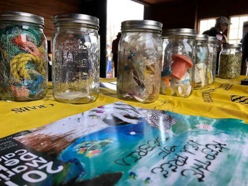 Samples of marine debris displayed in jars on a table.