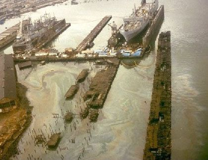 Ships in drydock; oil slicks all around dock area.