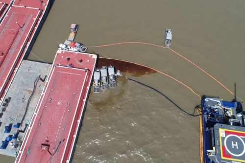 Overhead view of  docks and bow of ship with oil in the water.