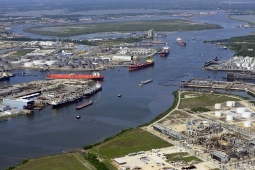 Overview of a channel, with a large tank farm and large vessels.