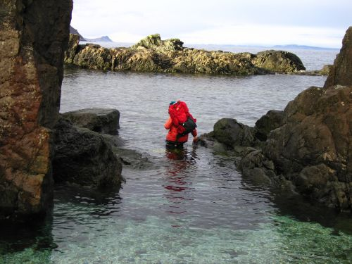 Person sampling in water between two boulders.
