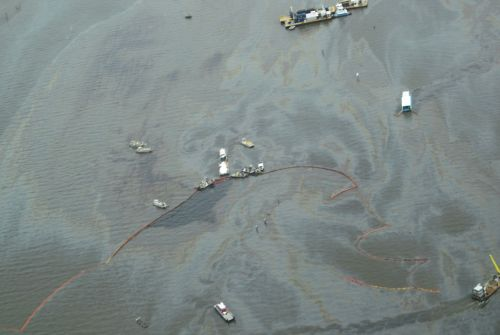 Overhead view of water with response vessels, boom and oily sheen.