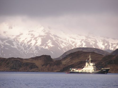 Tug boat on water with mountains behind.