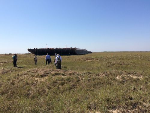 Barge in a field with bystanders looking on.