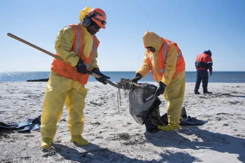 Two people in hazmat suits clean up oil from a beach.