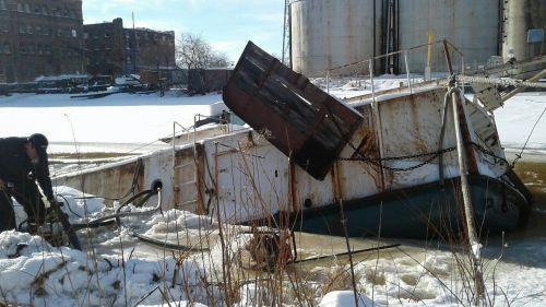 Sinking vessel near an industrial area.