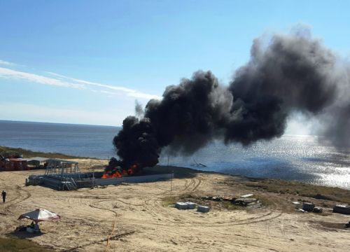 Black smoke rising from an area near a beach.