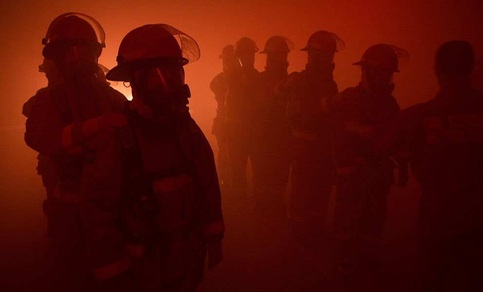 A silhouette of firefighters in a red haze.