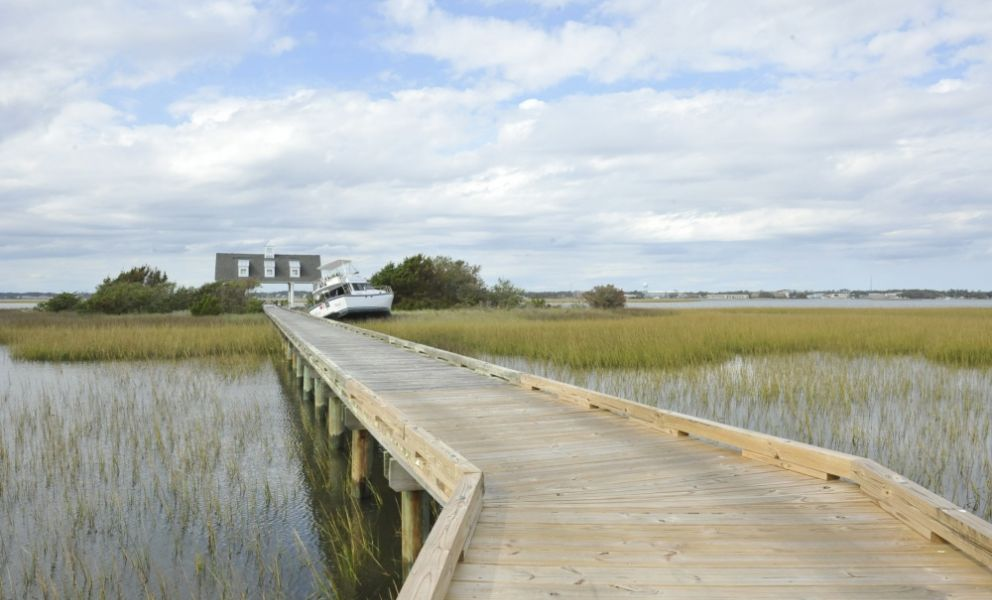 A boardwalk in the foreground leading to a marshland with a displaced vessel next to a building.