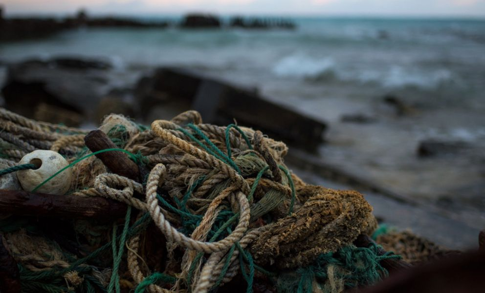 Debris, rope, on a beach with ocean in background.