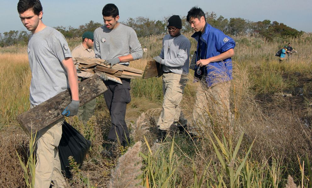 Americorps volunteers carry debris out of a marsh.