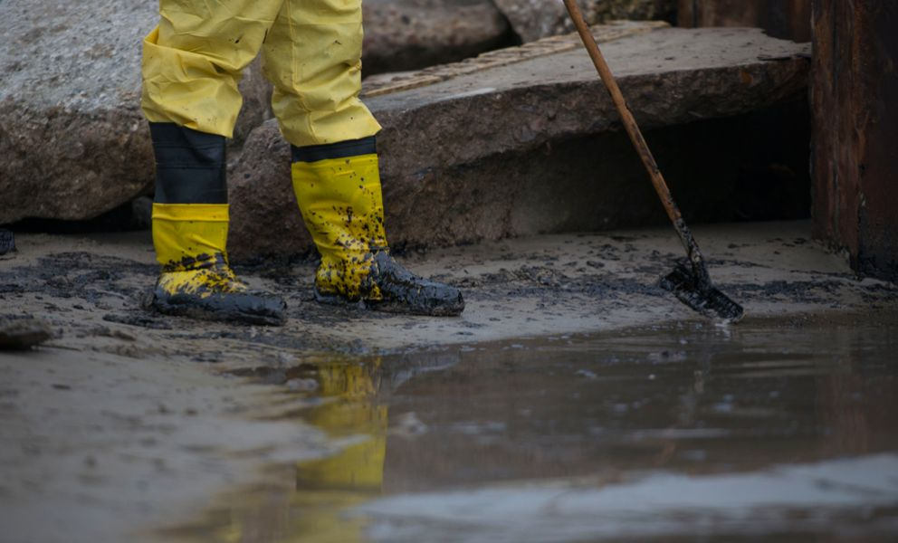 Boots of cleanup worker raking oil on sandy beach.