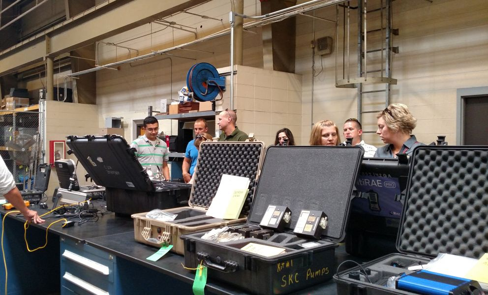 People learn chemical safety with equipment in a warehouse.