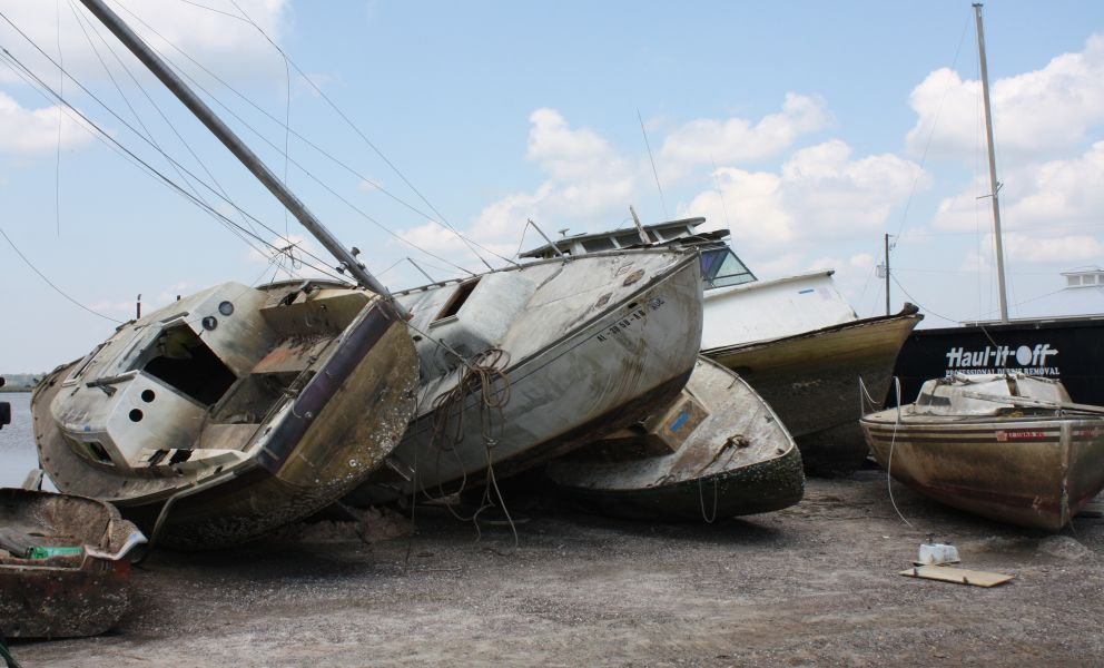 Old decrepit recreational boats piled on a dock.