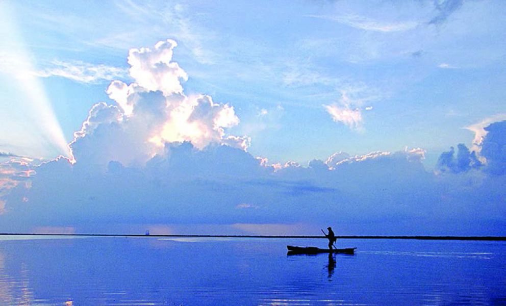 Person in boat paddling on Gulf of Mexico waters.