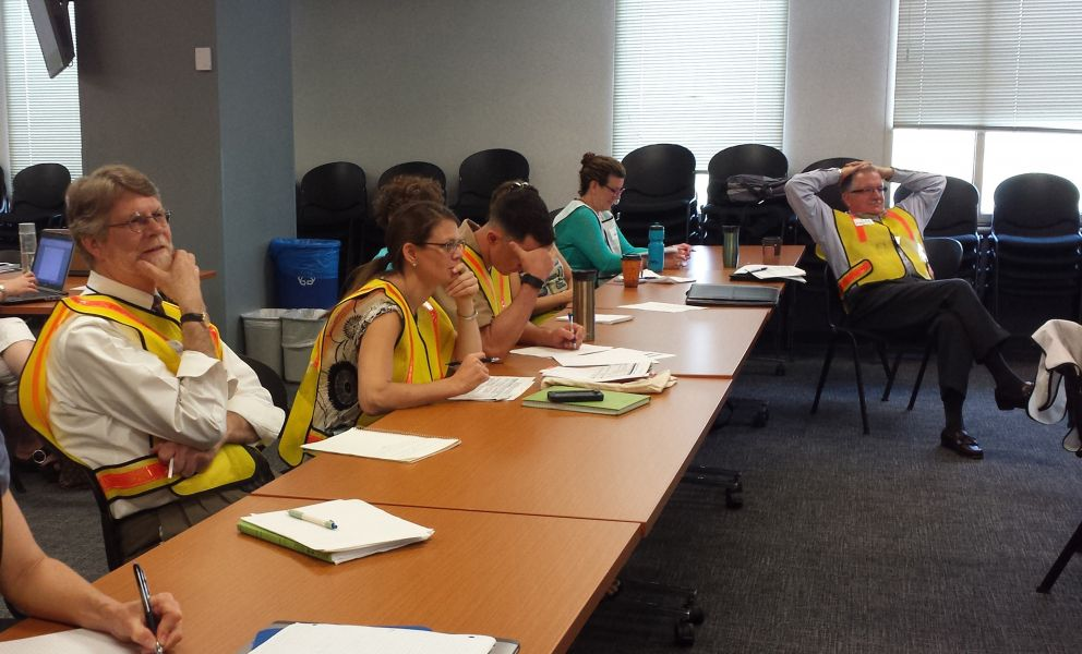 People in safety vests sitting at a table and taking notes.