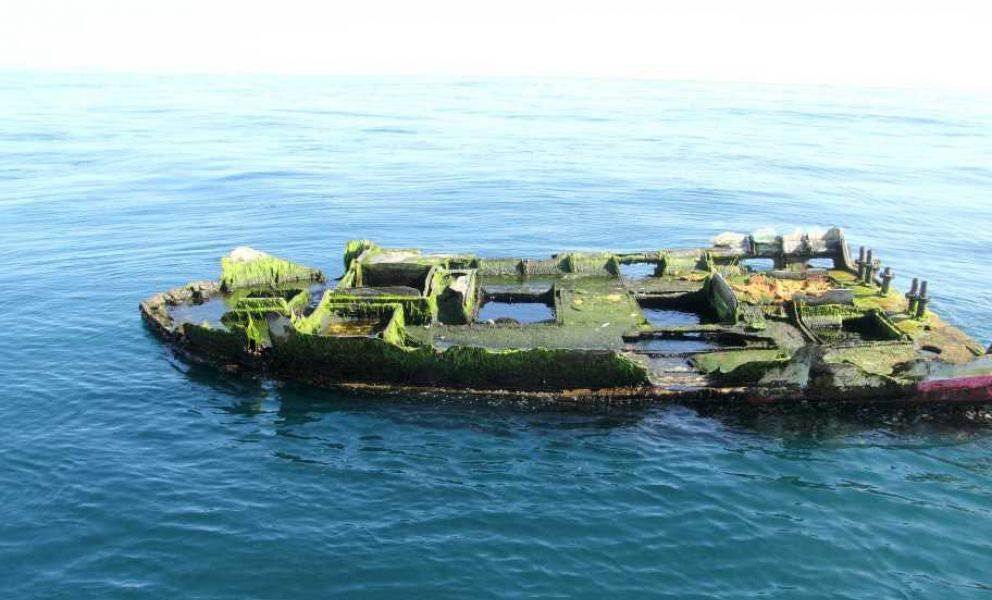 Partial decayed boat floats on the ocean.