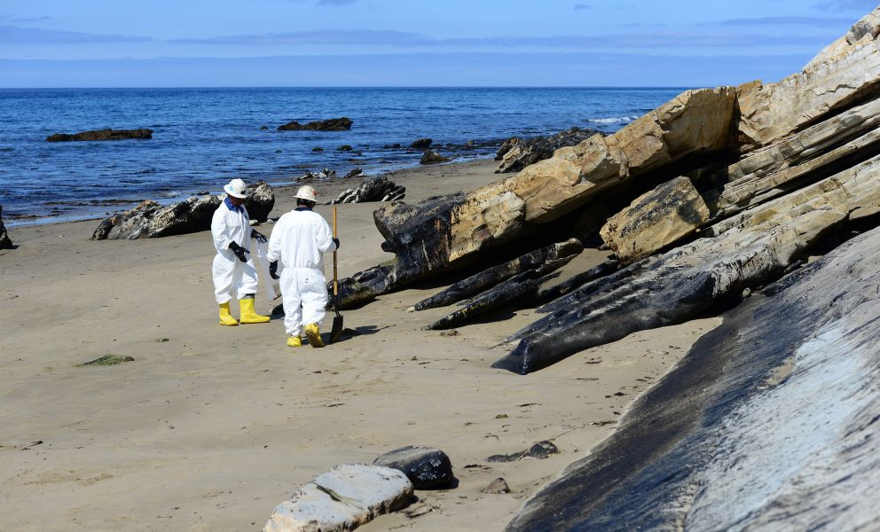 Two workers clean up a rocky and sandy oiled beach in California.