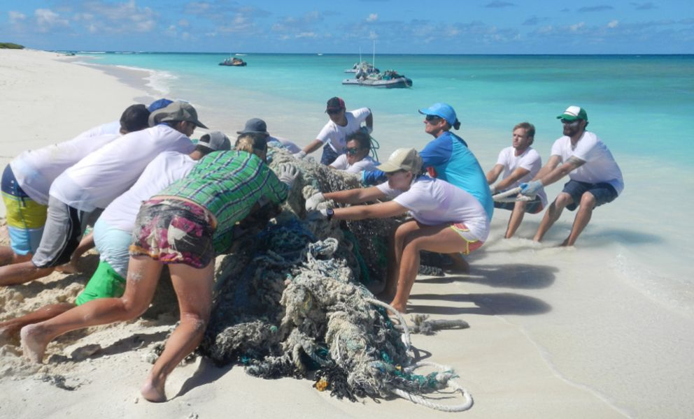Group of people pushing and pulling old fishing nets off a beach in Hawaii.