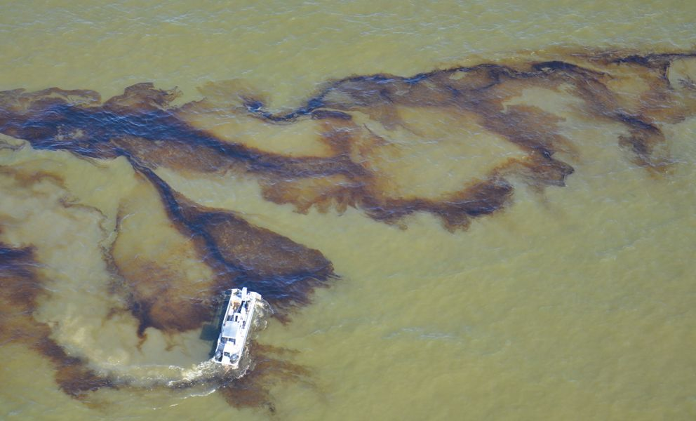 Boat on water near oil spill.