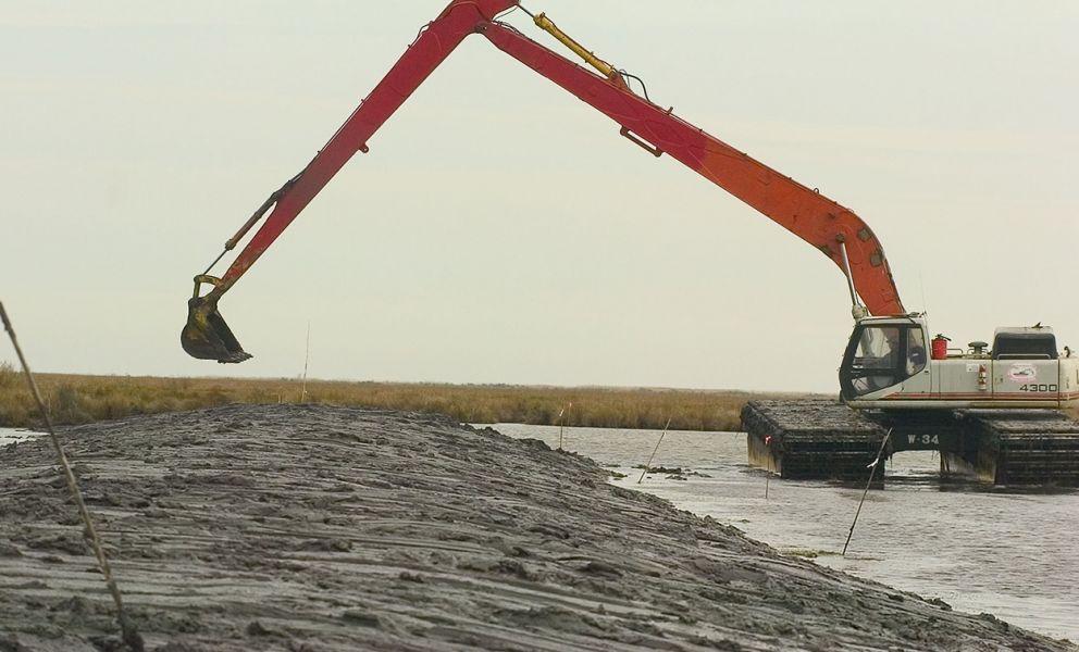 Red-armed hydraulic shovel scarping soil near water's edge.