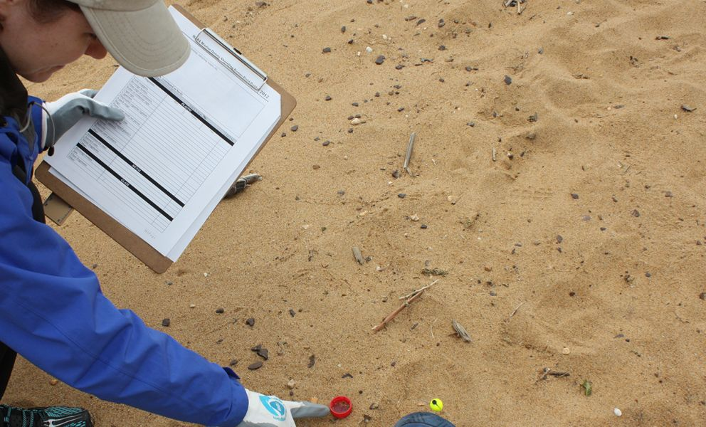 Person pointing at trash on sand.