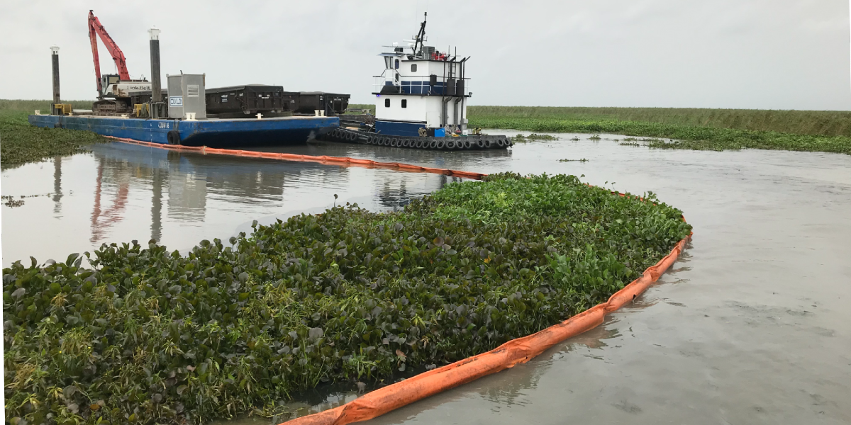 A vessel in marsh with pollution boom around it.