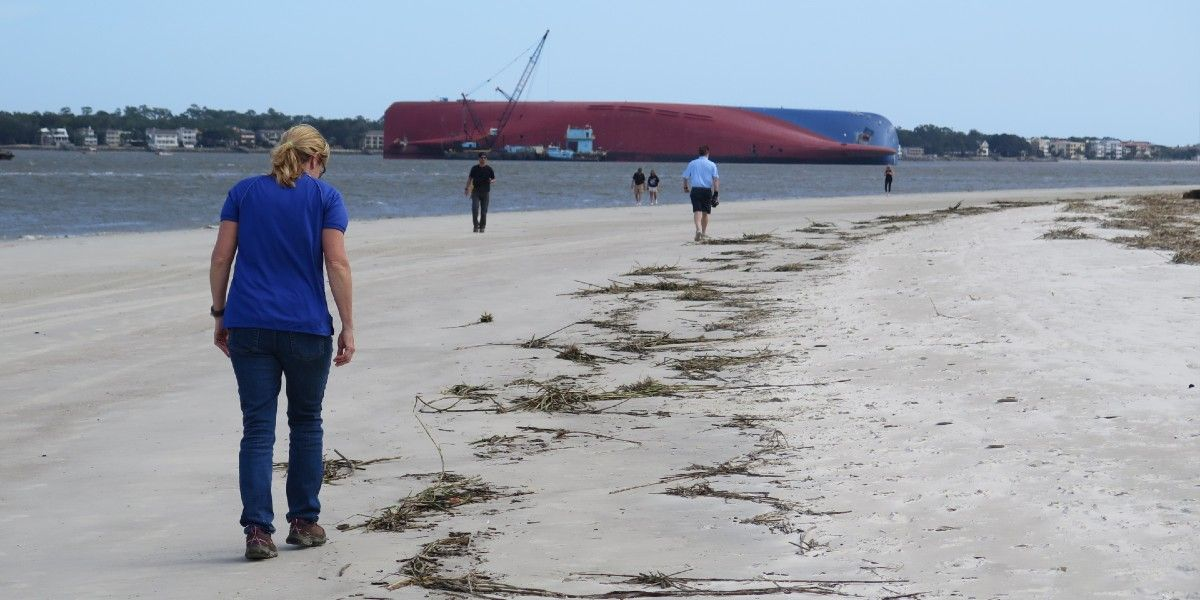 A woman walking on a beach with large overturned vessel in the background.
