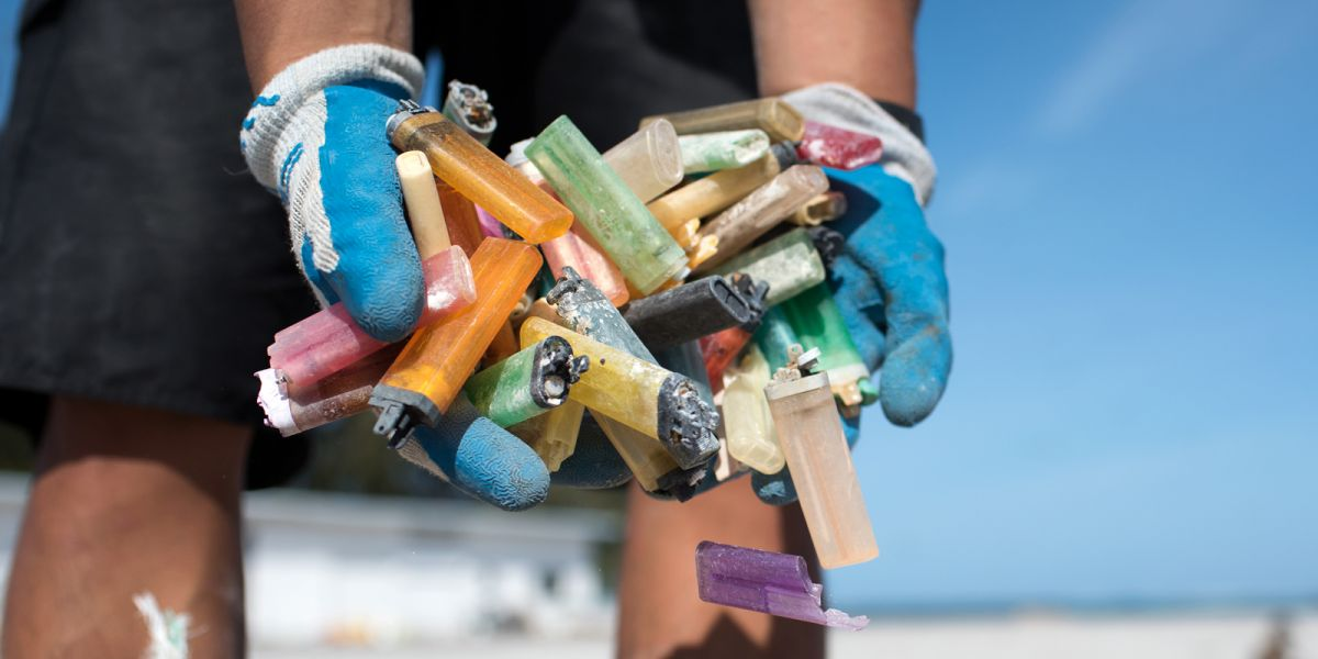 A person holding a handful of old lighters.