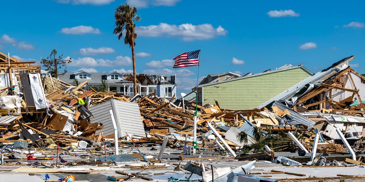 A palm tree and an American flag standing among wrecked buildings and other hurricane debris.