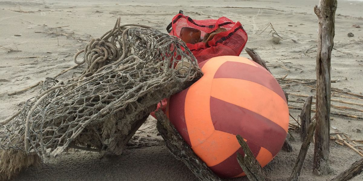 A derelict trap and several beach toys on a beach.