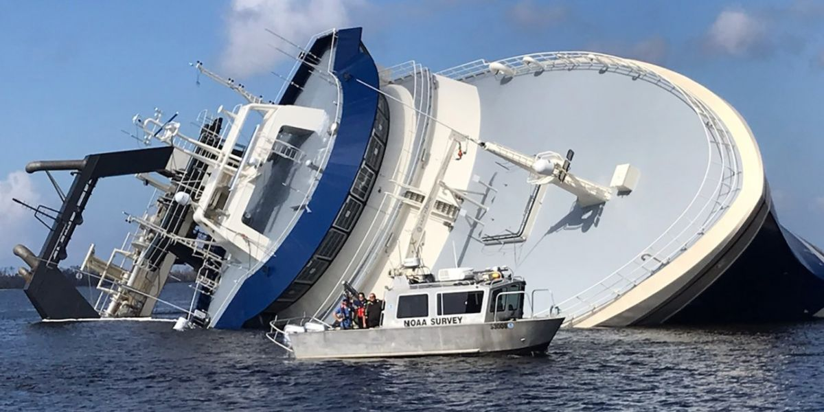 "A large vessel overturned on its side with a smaller vessel reading ""NOAA Survey"" in front of it."