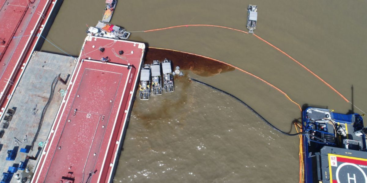 An aerial view of oil in a pollution boom along a barge.