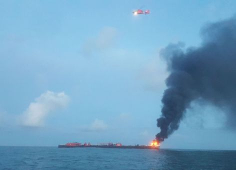 A helicopter flies over the barge. Smoke is seen billowing out from the flames on the bow.