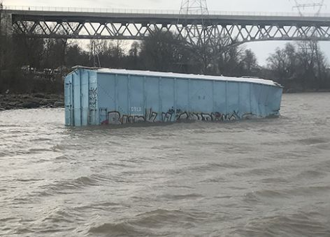 Rail car floating in a river.