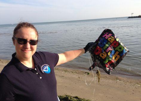 "A woman on a beach holding a deflated ""Happy Birthday"" balloon."