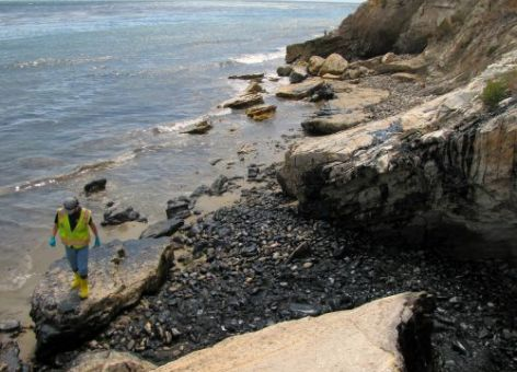 Cleanup worker and oiled boulders on Refugio State Beach where the oil from the pipeline entered the beach. Image: NOAA.