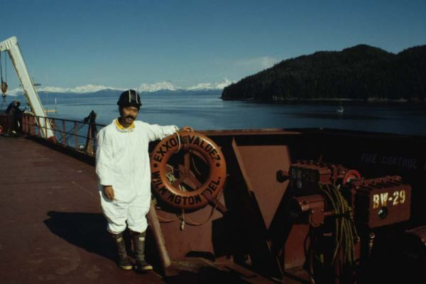 """A man on a boat with a life ring reading """"Exxon Valdez."""""""