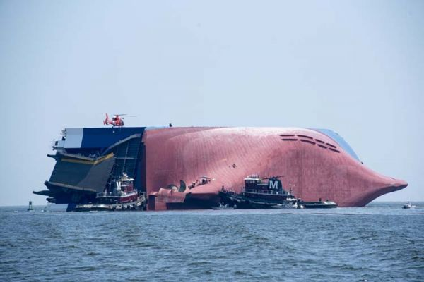 A large freighter vessel overturned on its site with a helicopter on it and several smaller vessels surrounding it.